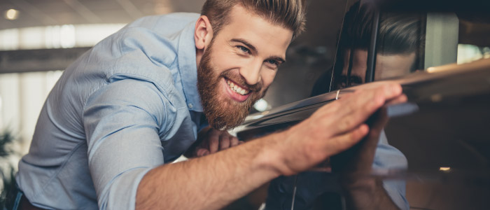 Happy man inspecting car at car dealership